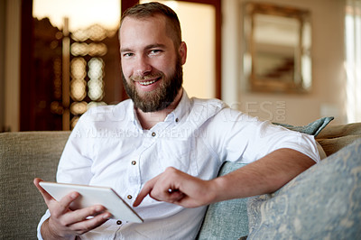 Buy stock photo Portrait of a young man using a digital tablet at home on the sofa