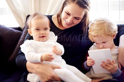Buy stock photo Shot of a little boy using a digital tablet while sitting with his family