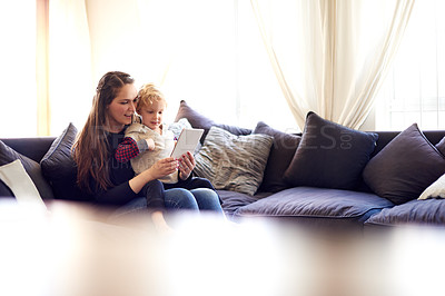 Buy stock photo Shot of a mother showing her little boy how to use a digital tablet
