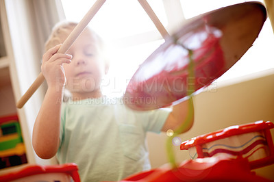 Buy stock photo Shot of a little boy playing with a toy drum set
