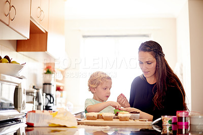 Buy stock photo Shot of a little boy helping his mom to decorate cupcakes