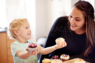 Buy stock photo Shot of a little boy holding cupcakes standing with his mom in the kitchen