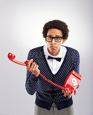 Buy stock photo Studio shot of a young man holding a telephone