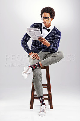 Buy stock photo Shot of a young man reading the newspaper while sitting on a stool against a gray background