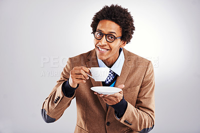 Buy stock photo Studio shot of a young man drinking out of a cup and saucer