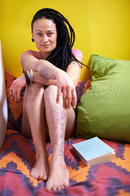 Buy stock photo Shot of a young woman with dreadlocks relaxing at home