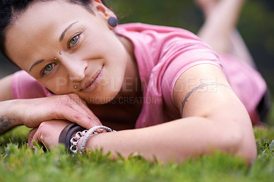 Buy stock photo Portrait of a woman relaxing on the grass outside