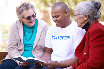 Buy stock photo Shot of a volunteer worker reading to two senior women