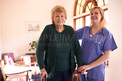 Buy stock photo Shot of a female nurse assisting a senior woman who's using a walker for support
