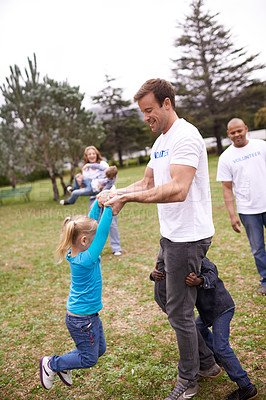 Buy stock photo Shot of a volunteer worker playing with children outdoors