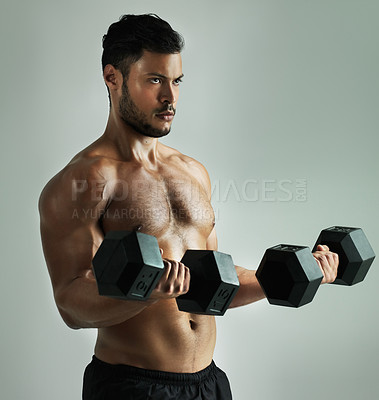 Buy stock photo Studio shot of a young man working out with dumbbells against a gray background