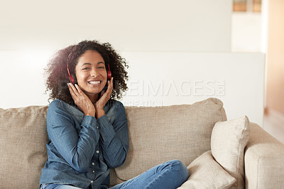 Buy stock photo Shot of a young woman listening to music on her headphones at home