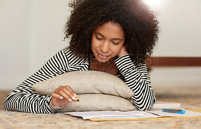 Buy stock photo Shot of a young woman lying on the floor while going over her notes at home