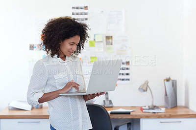 Buy stock photo Shot of a young designer working on her laptop in an office