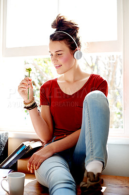 Buy stock photo Shot of a teenage girl listening to music while holding a white rose
