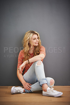 Buy stock photo Shot of a young woman sitting against a gray background