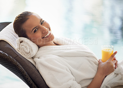 Buy stock photo Shot of a young woman drinking a glass of orange juice at the day spa