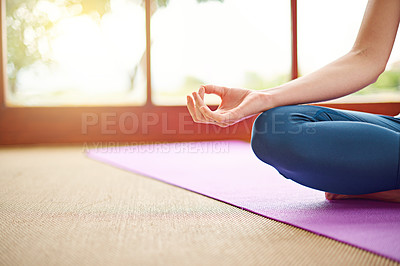 Buy stock photo Cropped shot of a woman meditating at home