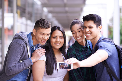 Buy stock photo Shot of a group of smiling university students taking a selfie together on campus