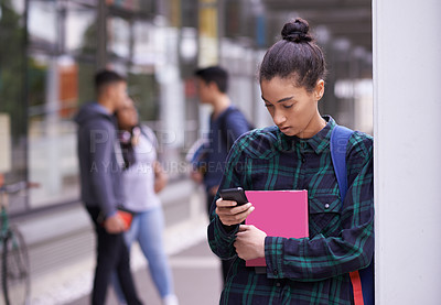 Buy stock photo Shot of a university student sending a text while standing on campus
