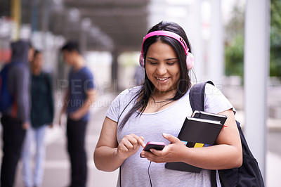 Buy stock photo Shot of a smiling university student listening to music while standing on campus
