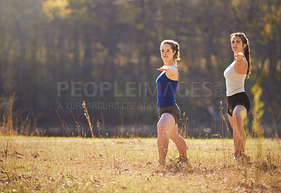 Buy stock photo Shot of two young women doing yoga in the outdoors