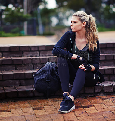 Buy stock photo Shot of a sporty young woman sitting outside with a gym bag