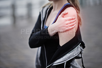 Buy stock photo Cropped shot of a young woman holding her injured shoulder