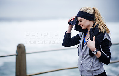 Buy stock photo Shot of a young woman wiping her forehead with a towel after a run