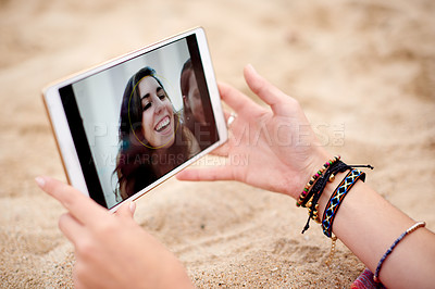 Buy stock photo Cropped shot of a woman looking at photos of her friends on her digital tablet