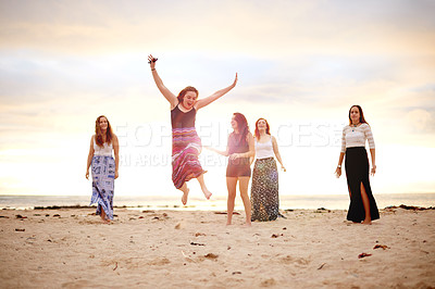 Buy stock photo Shot of young woman jumping in the air during a fun day at the beach with her girlfriends