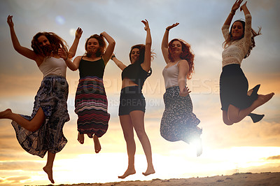 Buy stock photo Shot of a group of girlfriends jumping for joy outdoors