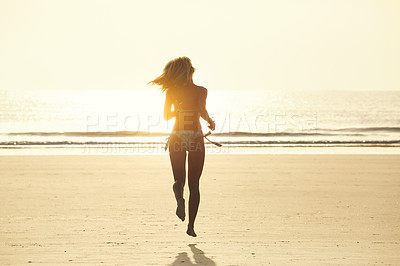 Buy stock photo Rearview shot of an attractive young woman running on the beach