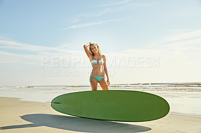 Buy stock photo Portrait of an attractive young woman standing behin her surfboard on the beach