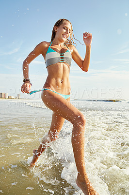 Buy stock photo Shot of an attractive young woman running on the beach