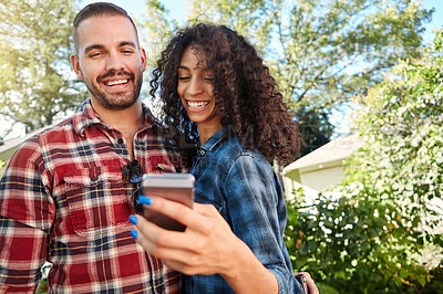 Buy stock photo Shot of a young couple standing outside looking at something on a cellphone