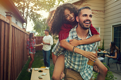 Buy stock photo Shot of a young man piggybacking his girlfriend with people standing in the background
