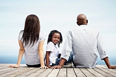 Buy stock photo Rearview shot of a young family sitting outside
