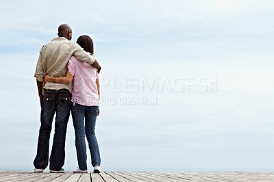 Buy stock photo Rearview shot of an affectionate couple standing arm in arm outdoors