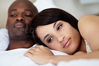 Buy stock photo Shot of a young couple lying in bed together
