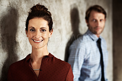 Buy stock photo Studio portrait of a smiling woman with her husband in the background