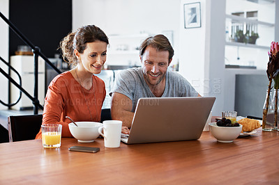 Buy stock photo Shot of a couple sitting at the dining table eating breakfast and using a laptop