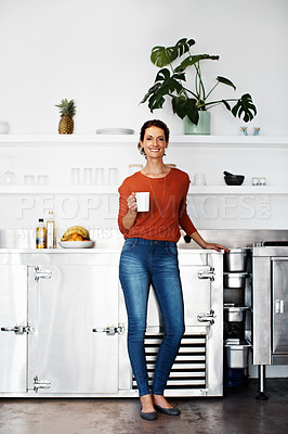 Buy stock photo Portrait of a woman standing in her kitchen drinking a coffee