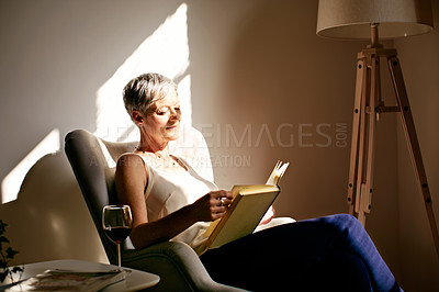 Buy stock photo Shot of a mature woman sitting in a chair reading in the sunlight