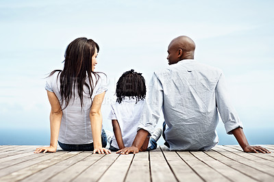 Buy stock photo Rearview shot of a young family sitting on a boardwalk outside