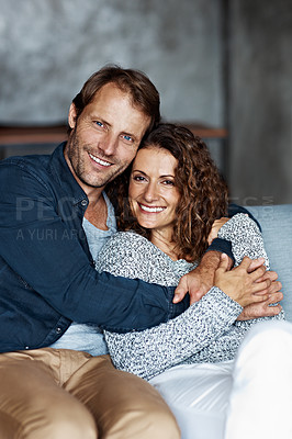 Buy stock photo Portrait of a smiling mature couple sitting on a sofa in their living room