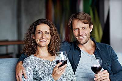 Buy stock photo Portrait of a smiling mature couple drinking wine while sitting on a sofa in their living room