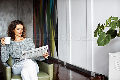 Buy stock photo Shot of a mature woman sitting in her living room drinking a coffee and reading the newspaper