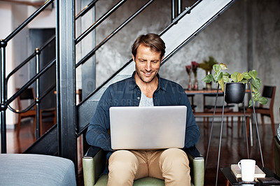 Buy stock photo Shot of a mature man sitting on a chair in his living room using a laptop