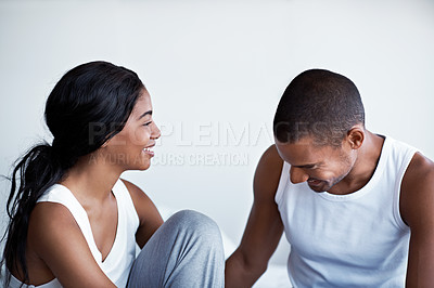 Buy stock photo Shot of young couple talking together while sitting on their bed